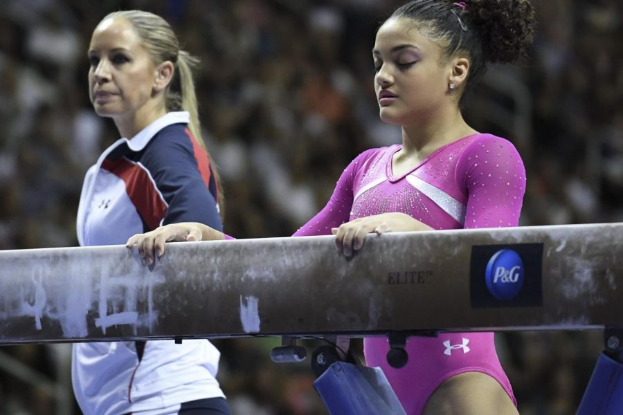 "Laurie Hernandez prepares to begin her beam routine during the women's gymnastics U.S. Olympic team trials in July of 2016. Her former coach Maggie Haney stands behind her. ""I thought they were just going to try to sweep it under the rug, but, wow, they did the right thing. I can't believe they actually did the right thing,"" said Hernandez, speaking about USAG."