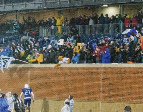 "Marc-Andre Thermitus '21 goes to celebrate with the HB student section after winning the state championship game. ""[The fans] were a huge part of playing that game, just the fact that so many people were willing to sit through that weather to support us really made a difference,"" said Blake Bergerson '21"