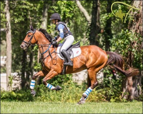 "Emma Armstong competing on her horse. The horse she is on is running through a course. ""I would like to make a name for myself through competing and continuing my riding education,"" said Armstong '21."
