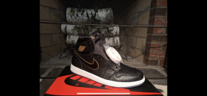 "The ""Air Jordan 1 Retro High OG 'City of Flight'"" is displayed on top of its shoebox. It was released in 2018, honoring Michael Jordan's first all-star game in 1985. The black tumbled leather upper with the translucent outsole and the golden highlights, all elements of this shoe work together to make it a bestseller."