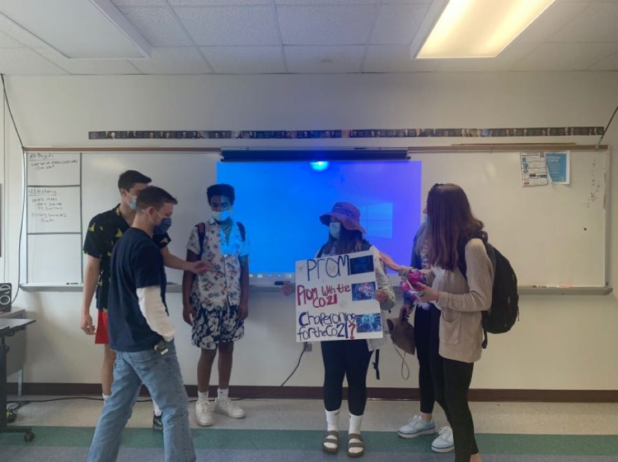 "Students of the senior class 'prompose' to Matthew Portu, asking him to chaperone for this year's prom during spirit week on Tropical Tuesday. Even with the changes to this year's spirit week, the students and staff are still able to have fun and show their spirit. ""Even though things are really different this year I'm still making the best of it by dressing up with friends, having fun costumes and trying to have the most spirit,"" said Julianna Cora '21."