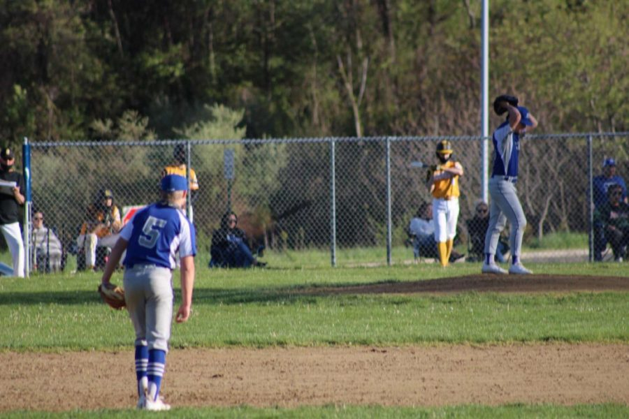 """Pitcher Brandon Hsu '21 mid-windup as Drew Gryniewicz '21 holds down the middle infield. The two seniors had big games, and their contributions helped out a whole team effort as almost every HB player got on base against Souhegan. """"We put hours in everyday this off-season training, and talking about our team and what we need to do as a team to be successful, so it's nice to see everything paying off and things executing the way we imagined."""""""